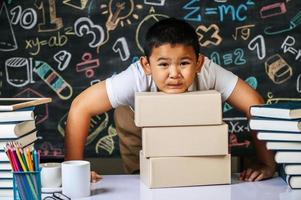 Child standing behind the boxes in the classroom photo