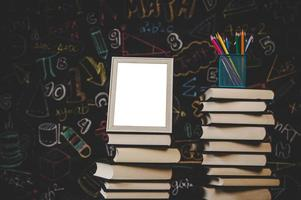 white photo frame and colored pencils on books in classroom