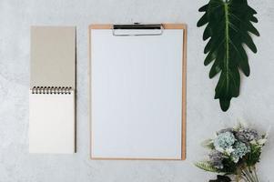 papel de nota, membrete y flores colocadas sobre un fondo blanco. foto