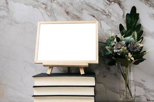 un marco de fotos colocado sobre un libro con un jarrón de flores
