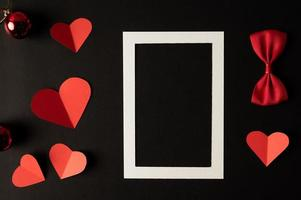 White photo frame and red heart paper pasted on a black background.