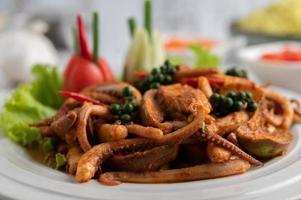 Calamares salteados con pasta de curry en plato blanco. foto