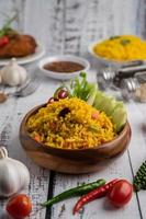 Turmeric rice in a Brown cup with spices on a white wooden floor photo