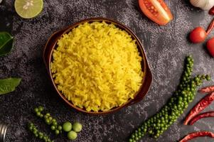 Turmeric rice in a brown cup with spices on black cement. photo