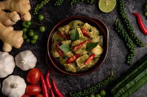 Pork green curry in a brown bowl with spices on a black cement photo