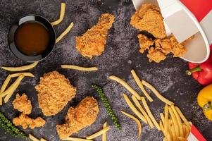 Fried Chicken and French Fries on Black Cement Floor. photo