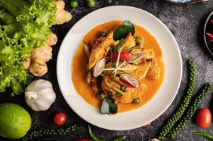 Dry green curry with chicken in white plates on black cement photo