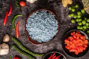 Butterfly Pea flower rice in a brown cup with spices on black cement. photo