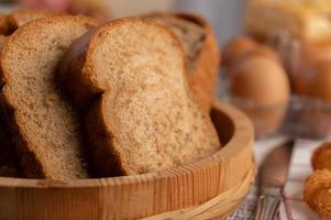 Bread slices placed in a wooden plate on a white wooden table. photo