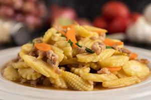 Stir-fried baby corn and carrots with minced pork in a white plate. photo