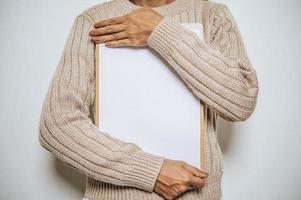 A people with long sleeves holds a clipboard on his chest. photo