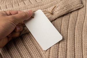A hand holding a white tag on a brown sweater. photo