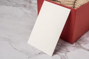 Postal y caja de regalo roja en tiempo de celebración. foto