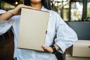 Woman holding a parcel box in cafe photo