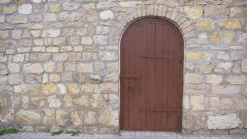Retro vintage stone brick wall and old wooden door background photo