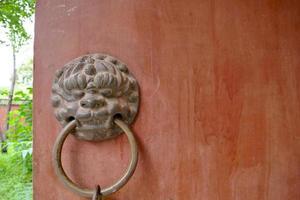 Ancient traditional red wooden door and metal lion door ring photo