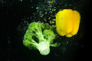 Photo of fresh vegetables falling in the water with bubble