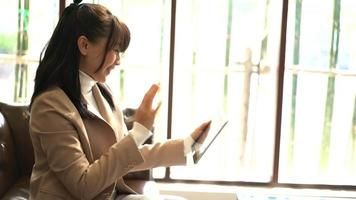 Business woman waving hand for greeting with video conference.