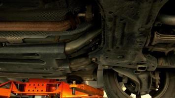 Vista inferior de un coche viejo en un ascensor en un taller de reparación video