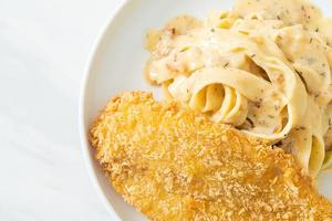Fettuccine pasta white cream sauce with fried fish photo