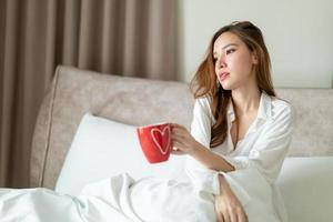retrato, mujer hermosa, despertar, y, tenencia, taza de café, o, taza, en cama foto