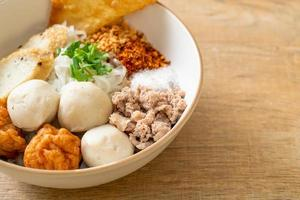 Spicy small flat rice noodles with fish balls and shrimp balls photo