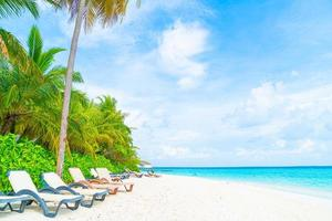 Beach chair with tropical Maldives resort hotel island and sea photo