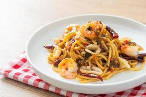 espaguetis picantes con mariscos en un plato foto