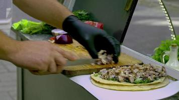 Streetfood-Verkäufer schneidet Fleisch für Wraps Burritos mit Messer video
