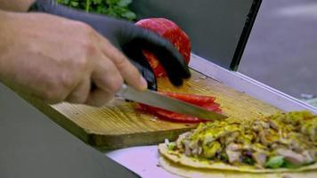 Straßenhändler, der Tomatenmesser auf hölzernem Fleischschneidebrett hackt video
