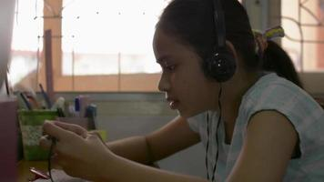 Girl wears headphones playing games with smartphone on the desk. video