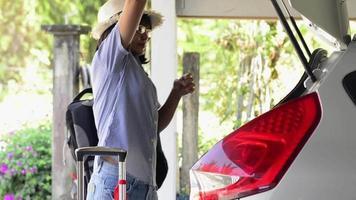 mulher se preparando para as férias com bagagem está carregando um carro. video
