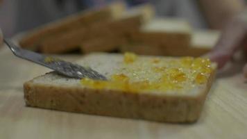 la mano de la gente extendiendo mermelada de naranja orgánica en pan de molde. video
