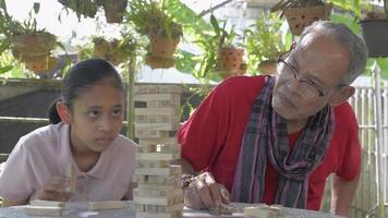 Grandfather and granddaughter playing wooden block tower together. video