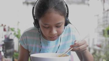 adolescente disfruta escuchando música desde el teléfono móvil durante el desayuno. video