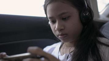Girl wears headphones playing games on smartphone sitting in a car. video