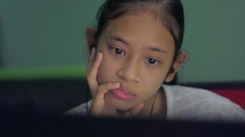 skolflicka bär hörlurar som studerar lektion online från bärbar dator hemma. video