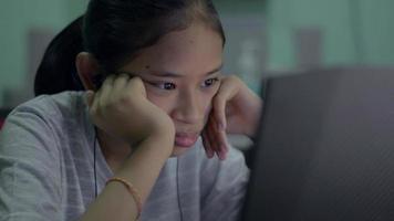 tråkig tjej som tittar på lektion online från bärbar dator på skrivbordet hemma. video