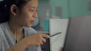 Girl explaining her homework via a computer online. video