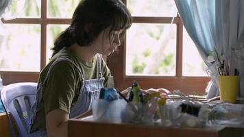 adolescente asiática trabalhando com tablet digital na mesa em casa. video