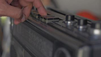 Man's finger presses a button to play old cassette tape player. video
