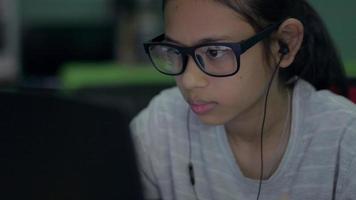 flicka i glasögon bär hörlurar med bärbar dator för att surfa webbplats. video
