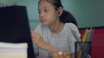 flicka som äter mat medan du tittar på lektion online från bärbar dator hemma. video