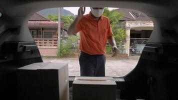 Delivery man open rear door of a car and carry a cardboard box to home video