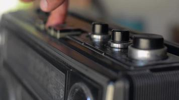 Man's hand presses button old cassette tape player and tune volume. video