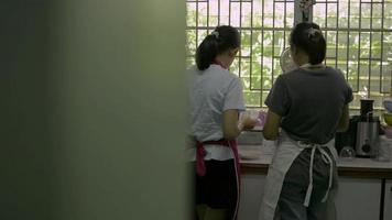 madre e hija vistiendo delantal limpiando utensilios de cocina. video