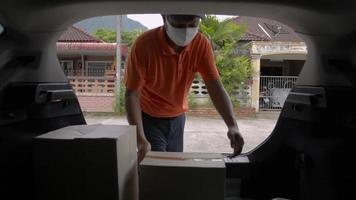 Delivery man open rear door of a van lift a cardboard box to a girl. video