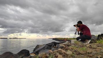 A photographer taking pictures at rocky shore in the sunset video