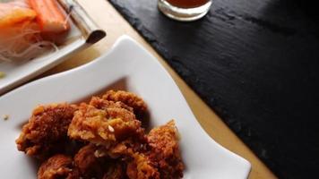 Zoom en cámara lenta de pollo frito y takoyaki en la mesa video