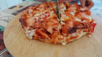 slow motion hand of asian woman cuts pizza with a knife. video